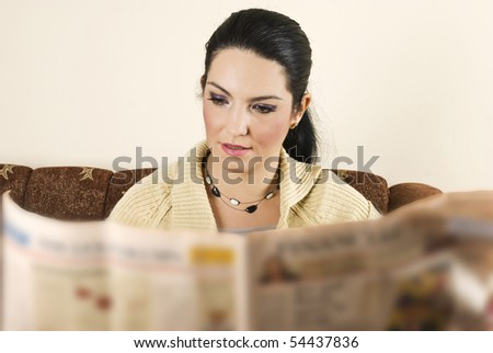 Young woman reading new in her home and sitting on sofa - stock photo