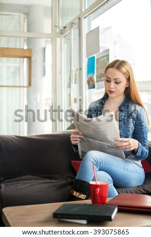 Young woman reading newspaper and having coffee break. - stock photo