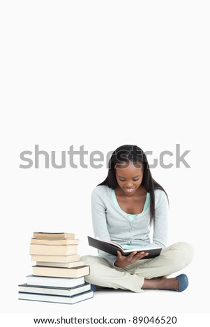 Young woman reading next to a pile of books against a white background - stock photo