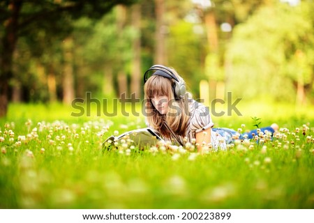 Young woman reading on nature, smiling and listening to the music - stock photo