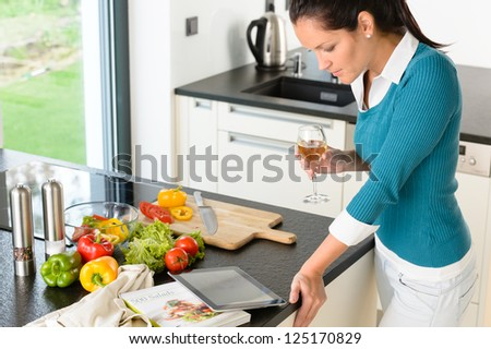 Young woman reading tablet recipe kitchen preparing food looking wine - stock photo