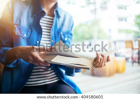 Young woman reading text book in library. - stock photo