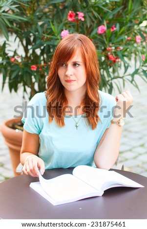 Young woman reading the book at the cafe outdoors