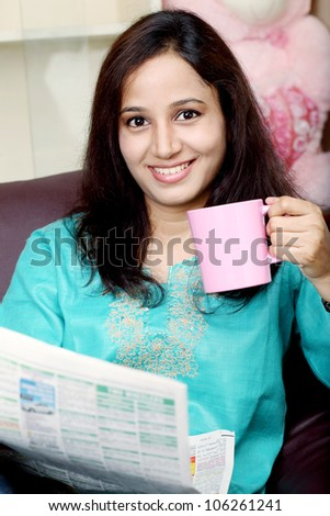 Young woman reading the newspaper and drinking coffee - stock photo