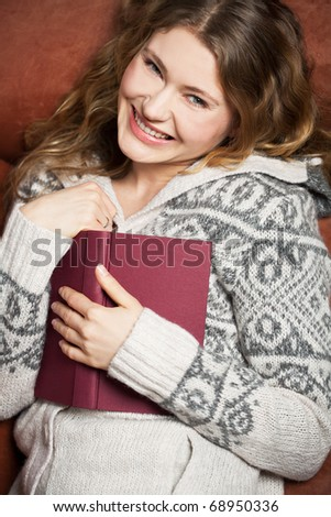young woman reads a book lying on a couch - stock photo