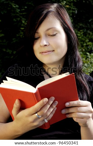 young woman reads a book outdoors