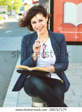 Young woman reads a book while waiting