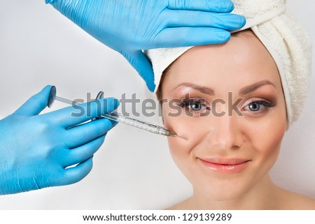 Young woman receiving a botox injection in her cheek - stock photo