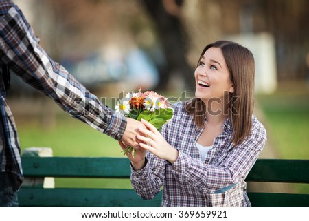 Young woman receiving a bunch of wild flowers on a date - stock photo