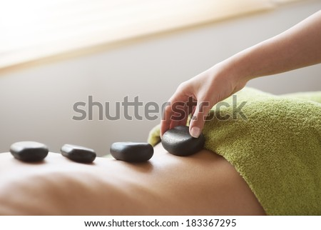Young woman receiving a hot stone massage therapy at spa.