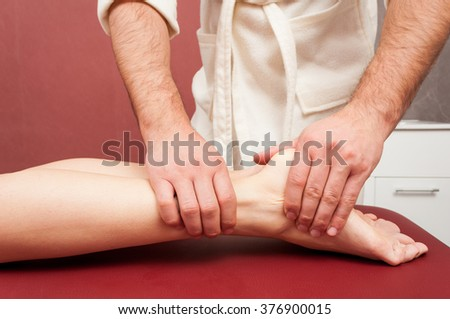 Young woman receiving a leg massage by masseur in the spa salon as relaxation concept