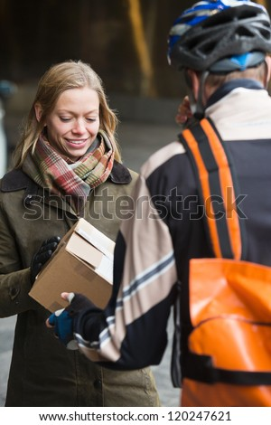 Young woman receiving a package from courier delivery man with backpack - stock photo