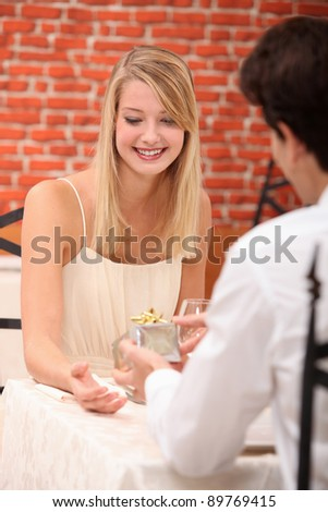 Young woman receiving a present in a restaurant - stock photo