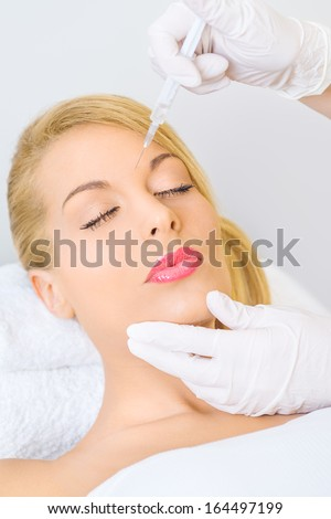 Young woman receiving cosmetic injection between eybrows - stock photo