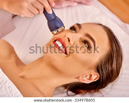 Young woman receiving electric facial massage at beauty  electroporation equipment. - stock photo