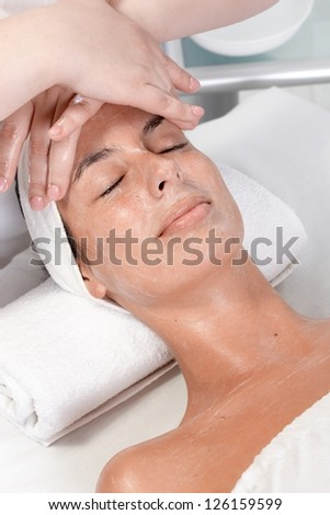 Young woman receiving face massage in dayspa, laying relaxed eyes closed. - stock photo