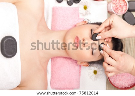 young woman receiving facial massage with mineral stone - stock photo