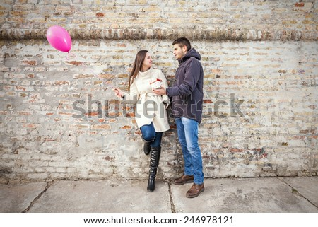 Young woman receiving gift from her boyfriend - stock photo