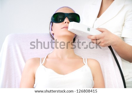 Young woman receiving laser epilation treatment on her upper lip - stock photo