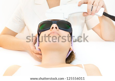 Young woman receiving laser therapy - stock photo