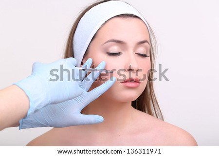 Young woman receiving plastic surgery injection on her face close up