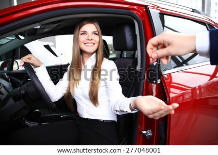 Young woman receiving the keys of her new car - stock photo
