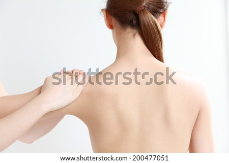 young woman receves chiropractic - stock photo