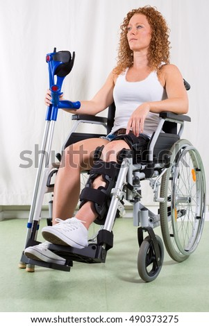 Young woman recovering from knee surgery sitting in a wheelchair with her leg in a brace holding crutches looking aside with a serious expression