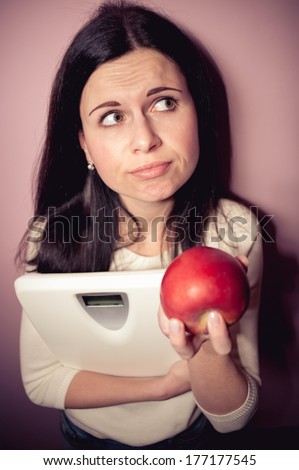 young woman reflects to grow thin her or not - stock photo
