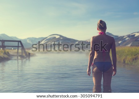 Young woman relax in a hot spring in Iceland Landmannalaugar - stock photo