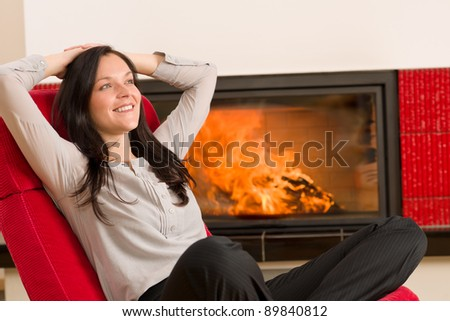 Young woman relax on red armchair by home fireplace - stock photo