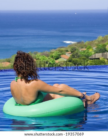 Young woman relaxes in a pool near the ocean - stock photo