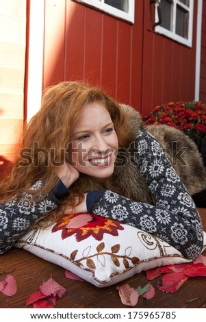 Young woman relaxes on a pillow in front of a summer house