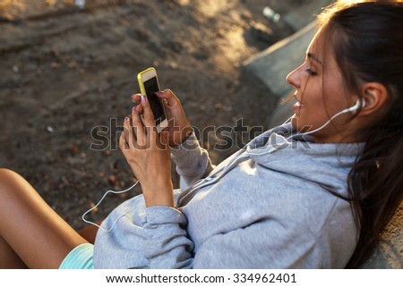 Young woman relaxing after jogging.She using her smart phone and listening to music.Typing message.leaning against wall.