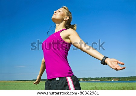 Young woman relaxing after running over blue sky, exercising and stretching outdoors, arms outstretched on summer sunny day. - stock photo