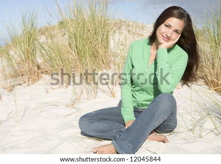Young woman relaxing amongst dunes looking to camera - stock photo