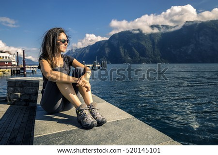 Young woman relaxing and enjoying the view on the fjord of Norway