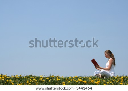 Young woman relaxing and reading a book outdoors, in a spring meadow. - stock photo