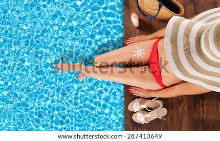 Young woman relaxing and sunbathing at swimming pool, sitting on wooden planks - stock photo