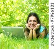 Young woman relaxing and using laptop in the park. - stock photo