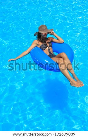 Young woman relaxing at the swimming pool in the summertime