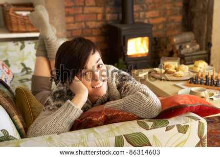 Young woman relaxing by fire - stock photo