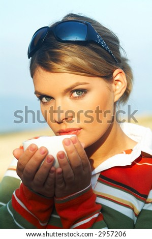 Young woman relaxing, drinking coffee at mountain outdoors