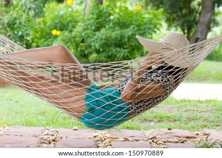 young woman relaxing in a hammock on a sunny summer day - stock photo