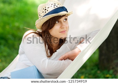 Young woman relaxing in a hammock with book - stock photo