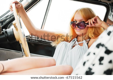 Young woman relaxing in a retro car. - stock photo