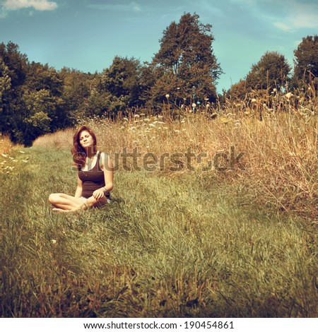 Young woman relaxing in a sunny field, instagram filter style - stock photo