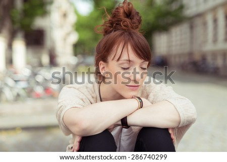 Young woman relaxing in a urban square sitting with her head resting on her arms over her bent knees with her eyes closed and a serene expression - stock photo
