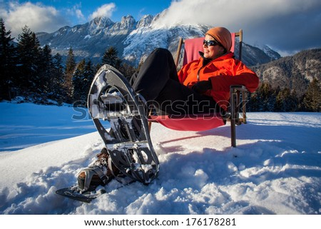 Young woman relaxing in an armchair with her snowshoes on.