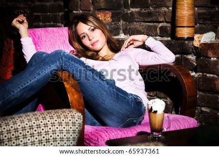 young woman relaxing in archair, indoor shot